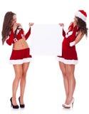 Mujeres de Santa que llevan a cabo a una tarjeta en blanco Imagen de archivo libre de regalías