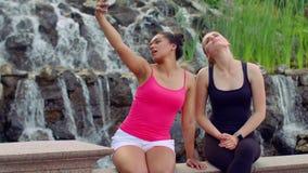 Mujeres de Selfie Dos mujeres jovenes que toman el selfie cerca de la cascada Selfie de las mujeres metrajes