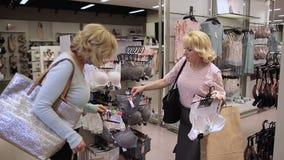 Mujeres de Shopaholics que seleccionan la lencería sexy en tienda almacen de metraje de vídeo