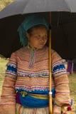 Mujeres de un Hmong de la flor debajo de un paraguas en Bac Ha Imagen de archivo libre de regalías