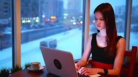 Mujeres de un negocios que trabajan con el ordenador portátil en café almacen de metraje de vídeo