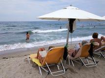 Mujeres debajo de los paraguas que se relajan en sunbeds mientras que otras personas que nadan imágenes de archivo libres de regalías