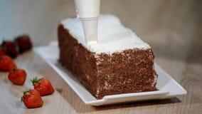 Mujeres del confitero que ponen la crema en la torta que acaba los pasteles metrajes