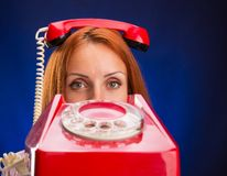 Mujeres del pelirrojo con el teléfono rojo Imágenes de archivo libres de regalías