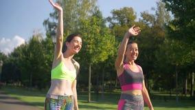 Mujeres deportivas alegres del ajuste que saludan a amigos en parque