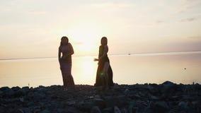 Mujeres despreocupadas en el baile negro largo del vestido en la playa en la puesta del sol almacen de video