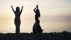 Mujeres despreocupadas en el baile negro largo del vestido en la playa en la puesta del sol metrajes