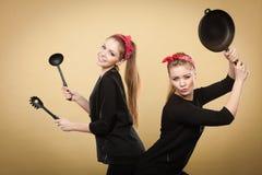 Mujeres diseñadas retras que se divierten con los accesorios de la cocina Fotos de archivo libres de regalías