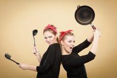 Mujeres diseñadas retras que se divierten con los accesorios de la cocina Imágenes de archivo libres de regalías