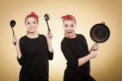 Mujeres diseñadas retras que se divierten con los accesorios de la cocina Fotografía de archivo libre de regalías
