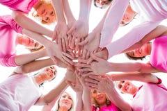 Mujeres diversas que sonríen en el rosa que lleva del círculo para el cáncer de pecho Imágenes de archivo libres de regalías