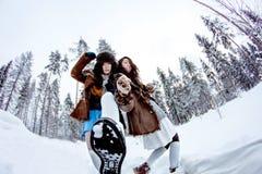 Mujeres divertidas que engañan alrededor en el fisheye blanco del fondo del invierno de la nieve Imágenes de archivo libres de regalías