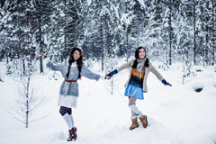 Mujeres divertidas que engañan alrededor en el fondo blanco del invierno de la nieve Fotos de archivo libres de regalías
