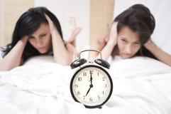 Mujeres durmientes enojadas que miran un reloj de sonido Foto de archivo libre de regalías