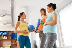 Mujeres embarazadas con el equipo de deportes en gimnasio foto de archivo