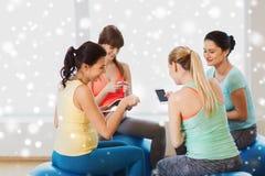 Mujeres embarazadas felices con los artilugios en gimnasio Imagen de archivo libre de regalías