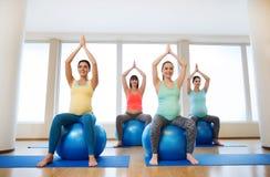 Mujeres embarazadas felices que ejercitan en fitball en gimnasio Imagen de archivo