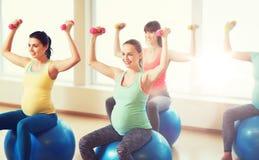 Mujeres embarazadas felices que ejercitan en fitball en gimnasio Imágenes de archivo libres de regalías