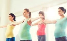 Mujeres embarazadas felices que ejercitan en gimnasio Imagen de archivo libre de regalías