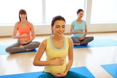 Mujeres embarazadas felices que ejercitan en la yoga del gimnasio Imagen de archivo