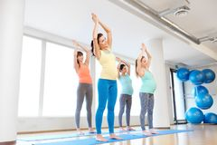 Mujeres embarazadas felices que ejercitan en las esteras en gimnasio Foto de archivo libre de regalías