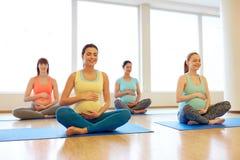 Mujeres embarazadas felices que ejercitan yoga en gimnasio fotografía de archivo
