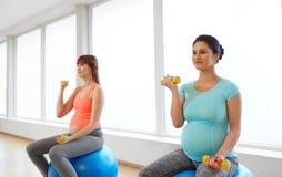 Mujeres embarazadas que entrenan con las bolas del ejercicio en gimnasio fotos de archivo libres de regalías