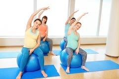 Mujeres embarazadas que entrenan con las bolas del ejercicio en gimnasio imagen de archivo
