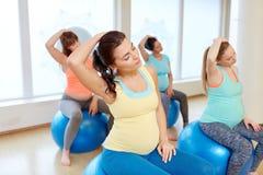 Mujeres embarazadas que entrenan con las bolas del ejercicio en gimnasio foto de archivo
