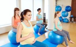 Mujeres embarazadas que se sientan en bolas del ejercicio en gimnasio fotos de archivo
