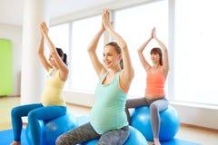 Mujeres embarazadas que se sientan en bolas del ejercicio en gimnasio fotos de archivo libres de regalías