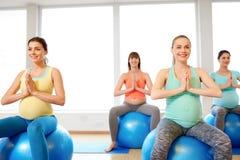 Mujeres embarazadas que se sientan en bolas del ejercicio en gimnasio imagen de archivo libre de regalías