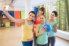 Mujeres embarazadas que toman el selfie por smartphone en gimnasio Foto de archivo