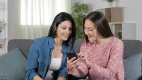 Mujeres emocionadas que comprueban el teléfono que celebra éxito