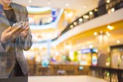 Mujeres en alameda de compras usando el teléfono móvil Imagen de archivo libre de regalías