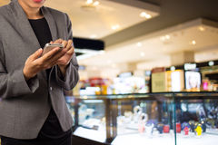 Mujeres en alameda de compras usando el teléfono móvil Fotos de archivo libres de regalías
