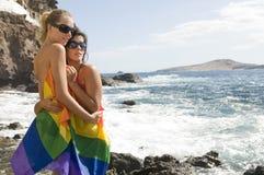 Mujeres en amor con el arco iris lesbiano plano Foto de archivo