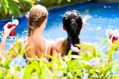 Mujeres en cócteles de consumición de la piscina asiática del hotel Imagen de archivo