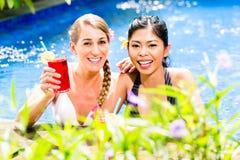Mujeres en cócteles de consumición de la piscina asiática del hotel Imagenes de archivo