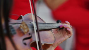 Mujeres en el músico rojo del vestido que juega el suplemento del violín almacen de metraje de vídeo
