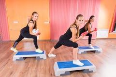 Mujeres en entrenamiento usando pesas de gimnasia y pasos aerobios Foto de archivo libre de regalías