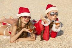 Mujeres en juego de la Navidad con martini en la playa Fotografía de archivo