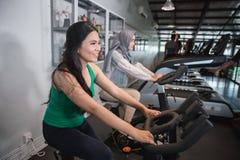 Mujeres en la gimnasia que hace ejercicios cardiios Imagen de archivo