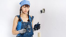 Mujeres en la profesi?n masculina: Una muchacha repara un interruptor el?ctrico con un destornillador y los alicates imagenes de archivo