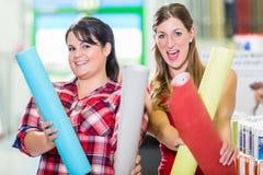 Mujeres en la tienda de las mejoras para el hogar que elige los papeles pintados Fotografía de archivo