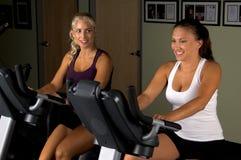 Mujeres en las bicis de ejercicio Fotografía de archivo