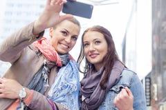 Mujeres en las chaquetas que toman el autorretrato a través del teléfono móvil Imagen de archivo libre de regalías