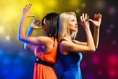 Mujeres en los vestidos de noche que bailan en el club Foto de archivo