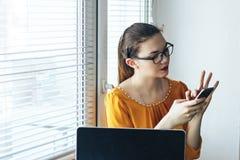 Mujeres en los vidrios que se sientan cerca de ventana cerca del ordenador que mira el teléfono móvil Imagen de archivo libre de regalías