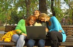 Mujeres en parque con la computadora portátil Fotografía de archivo libre de regalías